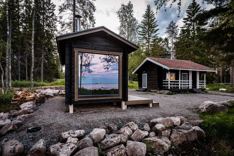 Ferienhaus in Finnland am See mit großem Fenster.