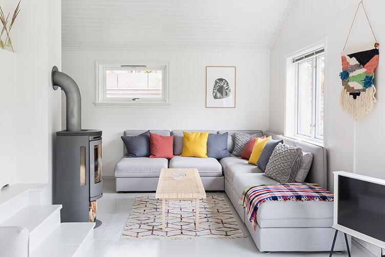 Schwedenofen und Sofa im Wohnzimmer im Ferienhaus an der norwegischen Küste bei Larvik