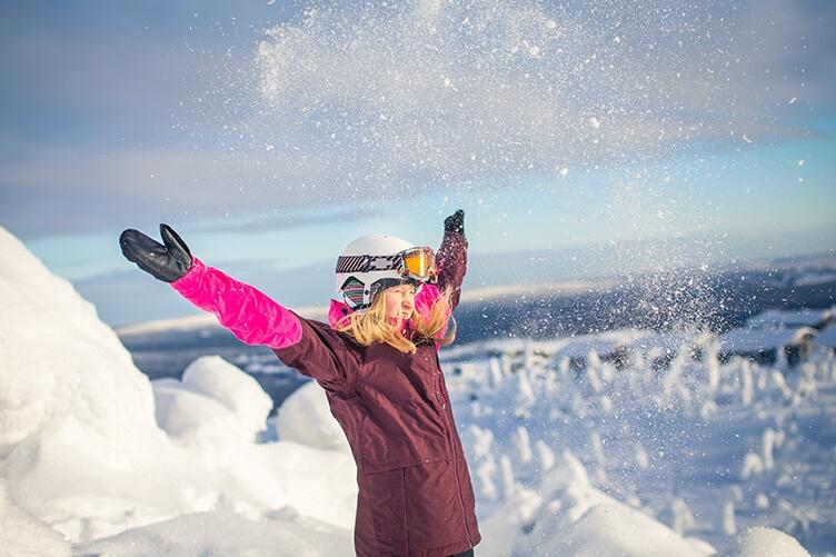 Kind im Urlaub im Schnee mit Skiausrüstung