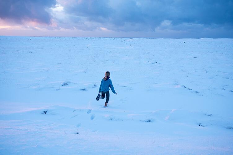 Ein Kind rennt über den Schnee in Island im Winter.